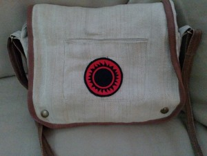 A bag with a black 3rd Imperium Sunburst on red field on it
